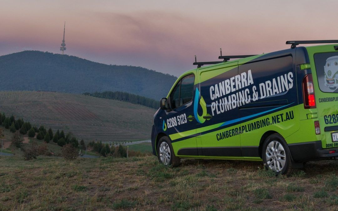 Plumber's van parked in Canberra with mountains in background.