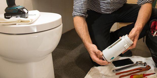 Plumber repairing a toilet